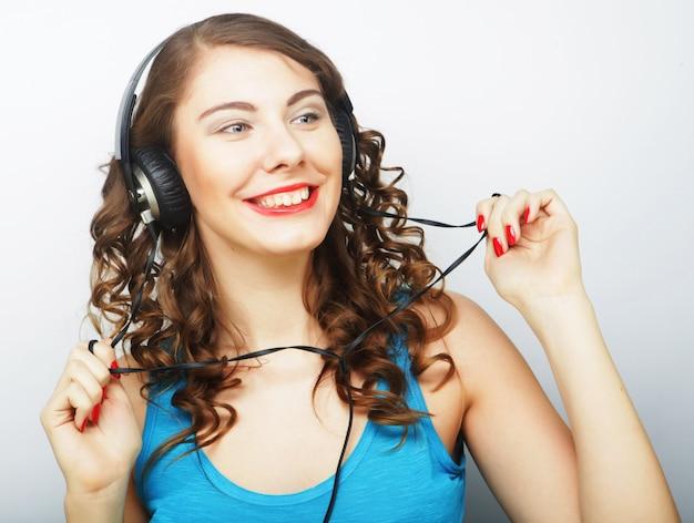 Giovane donna riccia con le cuffie che ascoltano la musica. colpo dello studio.