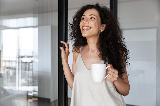 Giovane donna riccia con lunghi capelli scuri sorridente e guardando da parte, mentre in piedi vicino alla porta di vetro in casa con una tazza di tè
