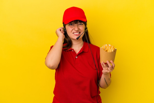 Giovane donna caucasica curvy ristorante fast food lavoratore tenendo patatine isolate su sfondo blu che copre le orecchie con le mani.