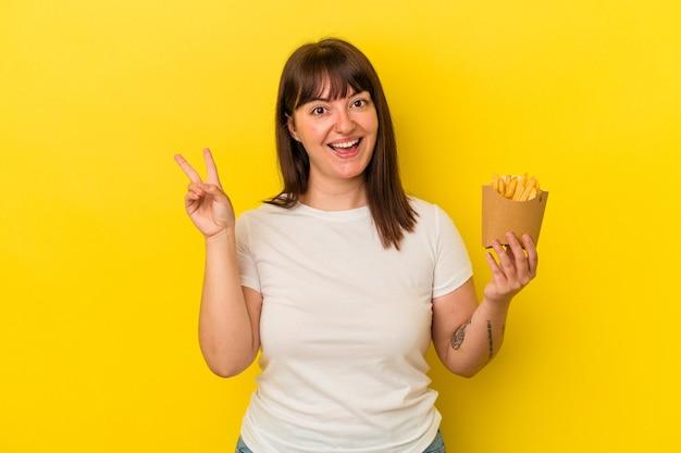Giovane donna caucasica curvy che tiene le patatine fritte isolate su fondo giallo gioiosa e spensierata che mostra un simbolo di pace con le dita.