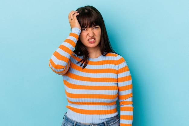 Giovane donna caucasica formosa isolata su sfondo blu dimenticando qualcosa, schiaffeggiando la fronte con il palmo e chiudendo gli occhi.