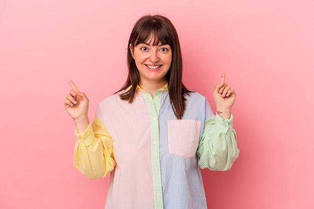 Giovane donna caucasica formosa isolata su sfondo rosa che punta a diversi spazi di copia, scegliendone uno, mostrando con il dito.
