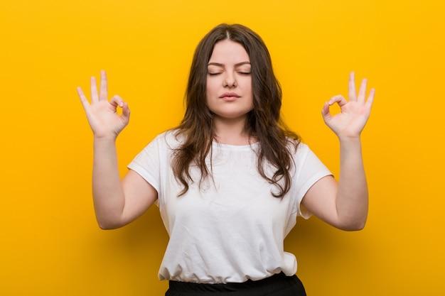 La giovane donna formosa più di dimensioni si rilassa dopo la dura giornata di lavoro, sta eseguendo yoga.
