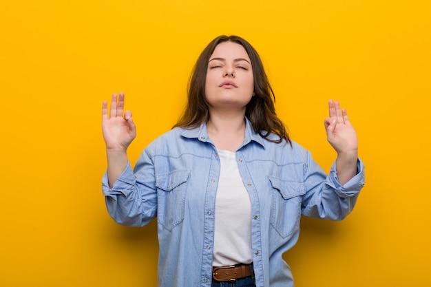Giovane donna formosa plus size si rilassa dopo una dura giornata di lavoro, sta eseguendo yoga.
