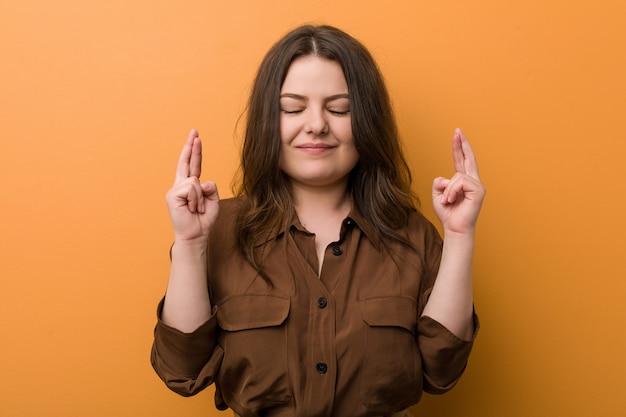 Giovane donna russa curvy che attraversa le dita per avere fortuna