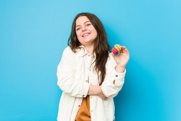 Giovane donna curvy che tiene amaretti ridendo e divertendosi.