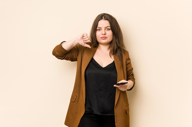 Giovane donna curvy in possesso di un telefono che mostra un gesto di avversione, pollice in giù. concetto di disaccordo.