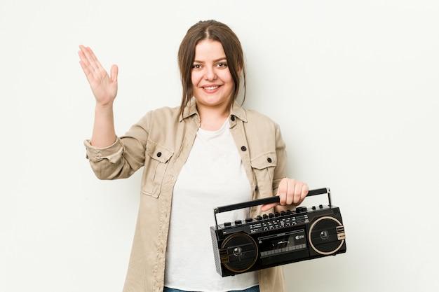 Giovane donna formosa in possesso di una radio retrò che riceve una piacevole sorpresa, eccitata e alzando le mani.