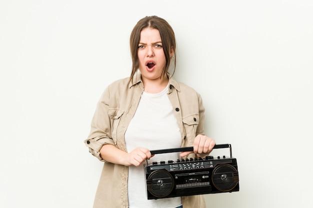 Giovane donna curvy che tiene una radio retrò che grida molto arrabbiata e aggressiva.