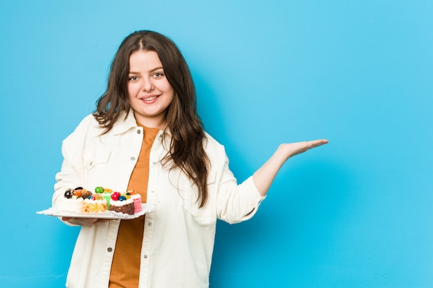 Giovane donna curvy che tiene una torta dolce che mostra uno spazio della copia su una palma e che tiene un'altra mano sulla vita.