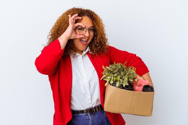 Giovane donna curvy che si trasferisce in una nuova casa isolata su sfondo bianco eccitata mantenendo il gesto ok sull'occhio.
