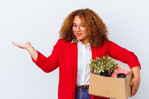 Giovane donna curvy che si trasferisce in una nuova casa isolata su sfondo bianco che mostra uno spazio di copia su un palmo e tiene un'altra mano sulla vita.