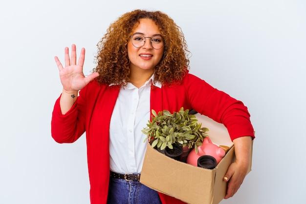 Giovane donna curvy che si trasferisce in una nuova casa isolata su sfondo bianco sorridente allegro che mostra il numero cinque con le dita.