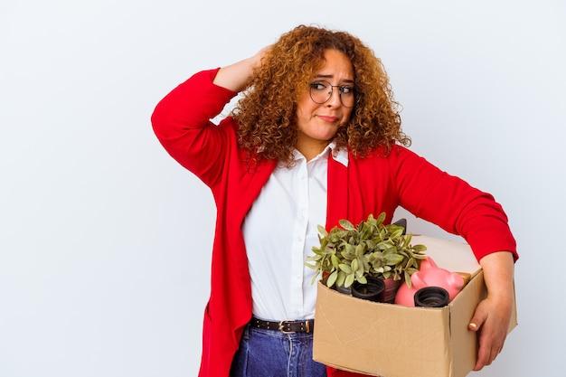 Giovane donna curvy che si trasferisce in una nuova casa isolata su sfondo bianco toccando la parte posteriore della testa, pensando e facendo una scelta.