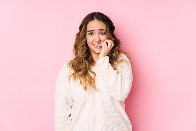 Giovane donna curvy in posa in un rosa isolato unghie mordaci, nervoso e molto ansioso.