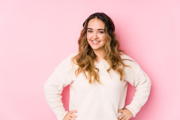 Giovane donna curvy in posa in un muro rosa isolato fiducioso mantenendo le mani sui fianchi.