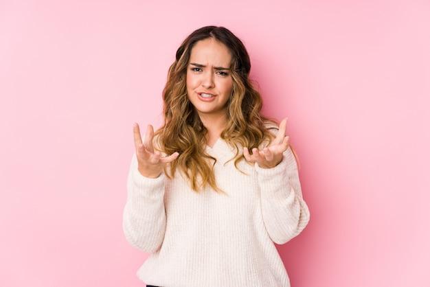 La giovane donna curvy che posa in una parete rosa ha isolato il ribaltamento che grida con le mani tese.