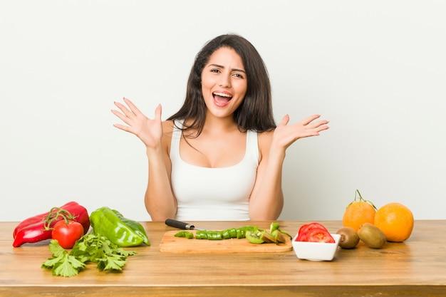 Giovane donna curvy che prepara un pasto sano per celebrare una vittoria o un successo, è sorpreso e scioccato.