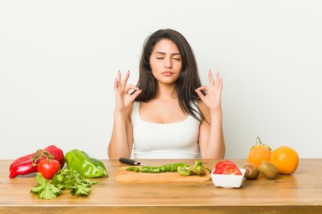 La giovane donna curvy che prepara un pasto sano si rilassa dopo una dura giornata di lavoro, sta eseguendo yoga.