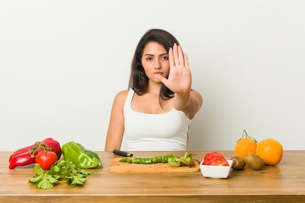 Giovane donna curvy che prepara un pasto sano che sta con il fanale di arresto di rappresentazione della mano tesa, impedendovi