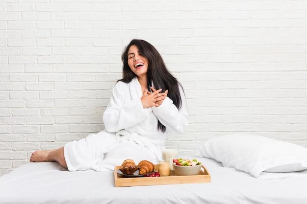 Giovane donna curvy che fa colazione sul letto ridendo tenendo le mani sul cuore, il concetto di felicità.