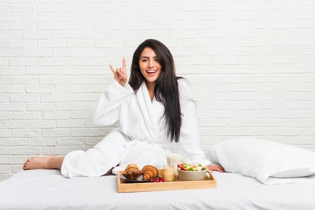 Giovane donna curvy che fa colazione sul letto che mostra un gesto di corna come un concetto di rivoluzione.