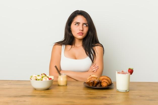 Giovane donna curvy prendendo una colazione stanca di un compito ripetitivo.