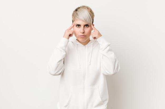 Giovane donna formosa che indossa una felpa con cappuccio bianca concentrata su un compito, tenendo gli indici puntati verso la testa.