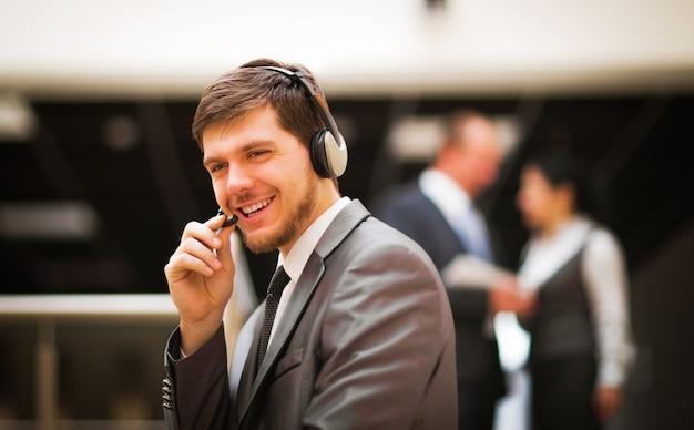 Giovane operatore del servizio clienti che parla all'auricolare sorridendo