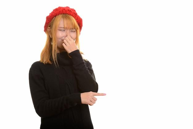 Giovane donna asiatica carina che copre il naso che punta il dito a lato