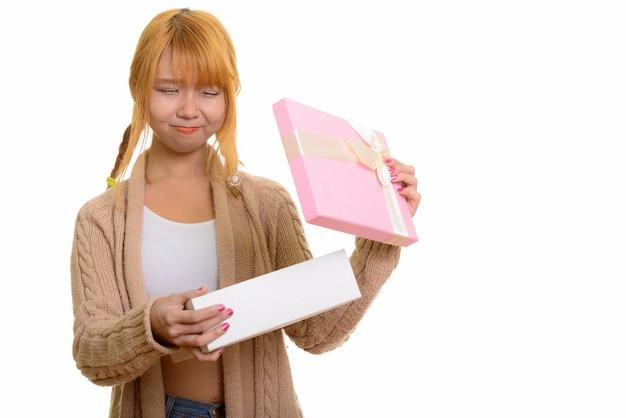 Contenitore di regalo di apertura della giovane donna asiatica sveglia che sembra deluso