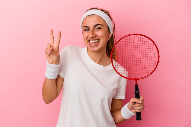 Giovane donna caucasica bionda carina che tiene una racchetta di badminton che mostra il numero due con le dita.