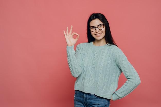 Giovane brunetta carina con gli occhiali vestito con un maglione lavorato a maglia turchese pastello