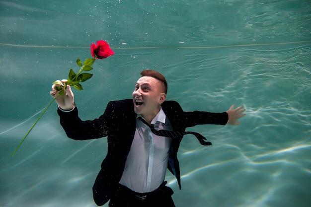 Il giovane uomo d'affari carino in tuta regala una rosa per san valentino o un anniversario in un appuntamento romantico sott'acqua. signore con rosa rossa
