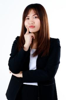 Giovane e carina imprenditrice in abito nero formale posa in gesto di pensiero su sfondo bianco.