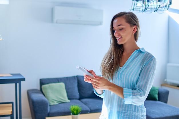 Giovane donna carina casual utilizzando il condizionatore d'aria e regolazione della temperatura confortevole con telecomando in appartamento