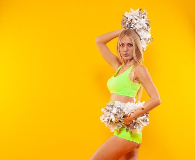 Giovane cheerleader carino con pompon isolato su sfondo giallo