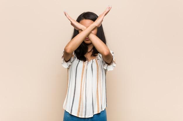 Giovane adolescente cinese carino giovane donna bionda che indossa un cappotto contro uno spazio rosa mantenendo due braccia incrociate, concetto di negazione.