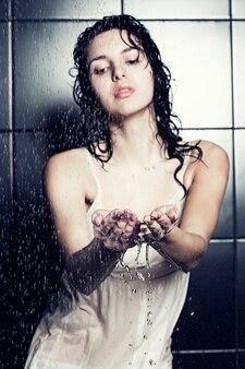 Giovane ragazza carina riccia facendo la doccia Foto Premium