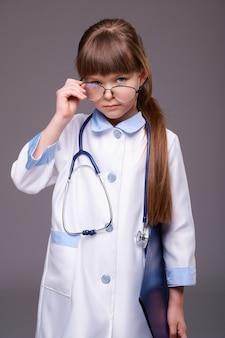 Giovane ragazza carina medico con lo stetoscopio che indossa occhiali da vista tiene la cartella con i documenti su sfondo grigio isolato