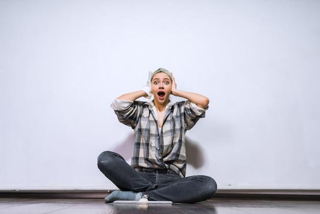 Giovane ragazza carina seduta sul pavimento, molto sorpresa, ripara nell'appartamento