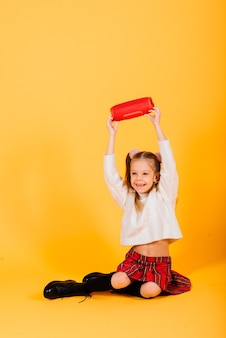 Giovane ragazza carina sorridente e balli con altoparlante portatile wireless su sfondo giallo studio. umore del nuovo anno.
