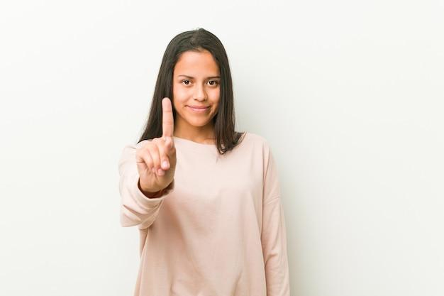 Giovane donna carina adolescente ispanica che mostra il numero uno con il dito.