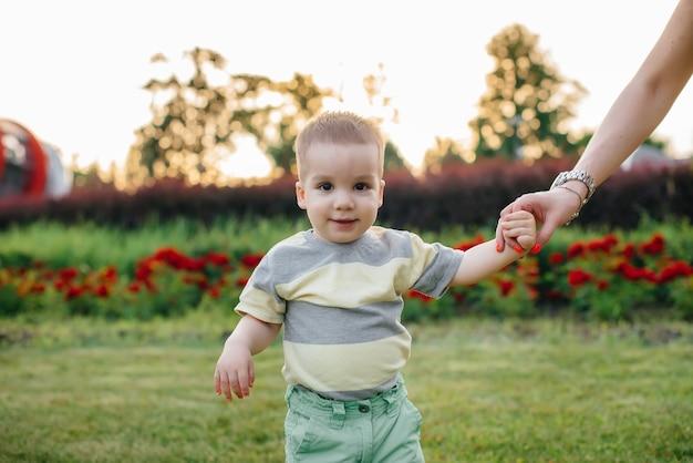 Una giovane madre carina aiuta e insegna al suo piccolo figlio a muovere i primi passi durante il tramonto nel parco sull'erba.