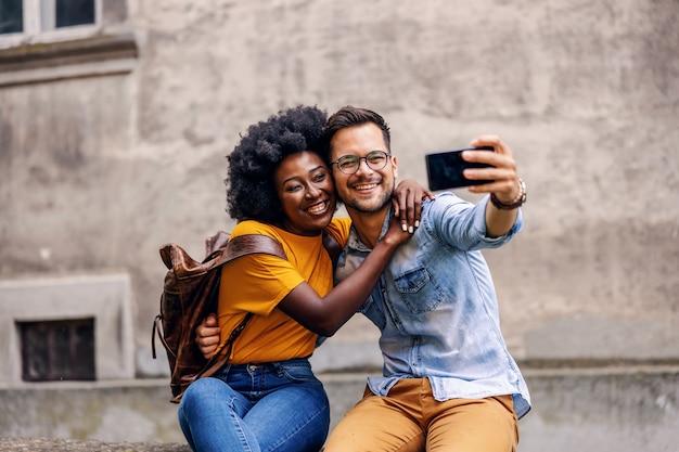 Coppia giovane carino hipster multiculturale abbracciando e prendendo selfie in una parte vecchia della città.