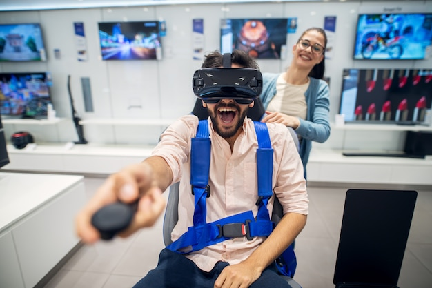 Giovane coppia stupita giocosa carina divertendosi con occhiali vr nel negozio di tecnologia.