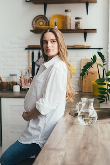Giovane ragazza incinta carina che beve acqua pulita in cucina