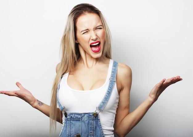 Giovane ragazza bionda sorridente carina su sfondo bianco