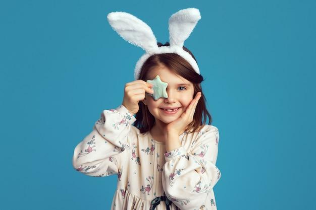 La giovane ragazza carina e sorridente indossa orecchie da coniglio e copre l'occhio con un biscotto a forma di stella star