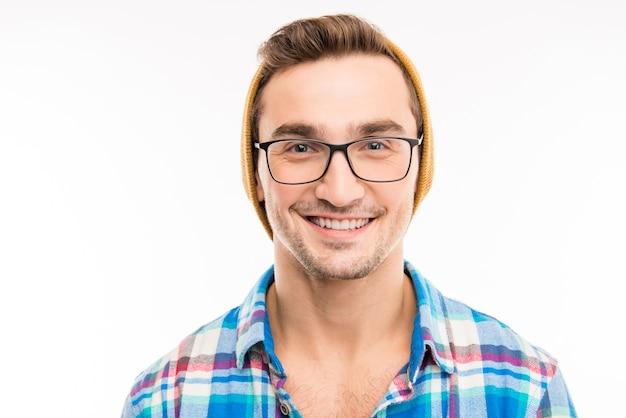 Giovane carino sorridente hipster in occhiali e cappello giallo
